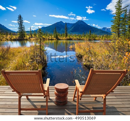 Two comfortable wooden chairs and a small round table on the lake. Concept of ecological tourism. Indian summer in the Rocky Mountains of Canada
