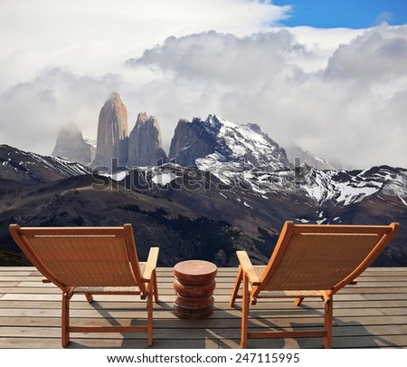 Two comfortable wooden deck chairs are on the platform overlooking the cliffs Torres del Paine - stock photo