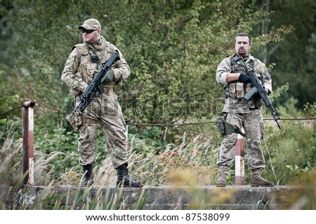 Two commandos patrolling,on the bridge - stock photo