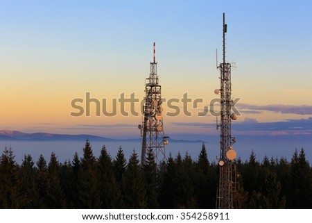 Two Communication Towers with Antennas, Dusk Blue Sky, Located in The Czech Republic -  Mobile Telecommunications System - stock photo