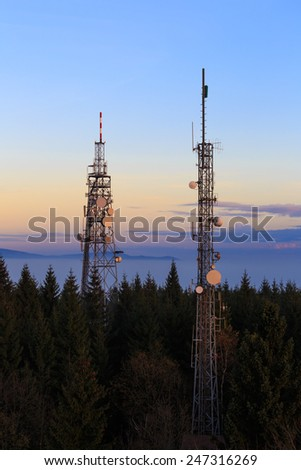 Two Communication Towers with Parabolic and GSM Antennas on Dusk Blue Sky, Located in The Czech Republic - Cerna Studnice - stock photo