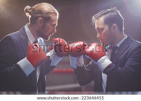 Two competitive businessmen in suits and boxing gloves attacking one another - stock photo