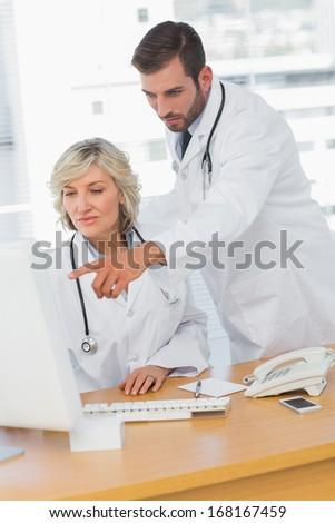 Two concentrated doctors using computer at medical office