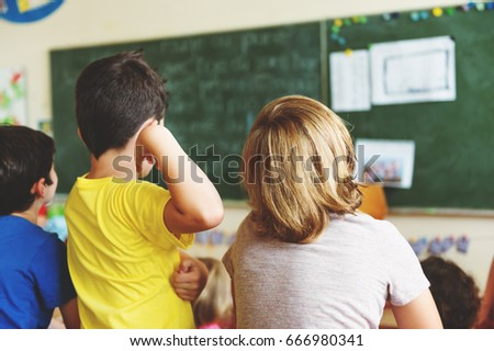 Two concentrated 4-5 year old boys in classroom, back view
