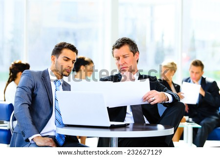 Two confident business people in formalwear discussing something while sitting at the office - stock photo
