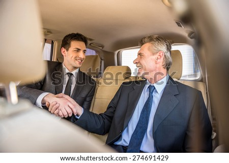 Two confident businessmen shaking hands and smiling while sitting in the car. - stock photo