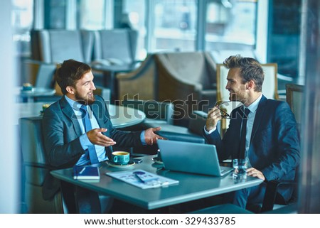 Two confident businessmen sharing their ideas and opinions - stock photo