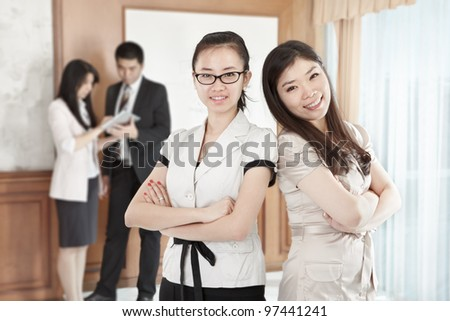Two confident businesswomen posing in the office - stock photo