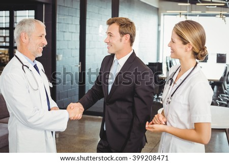 Two confident doctors standing in hospital and shake their hands - stock photo