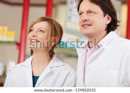 two confident pharmacists looking up - stock photo