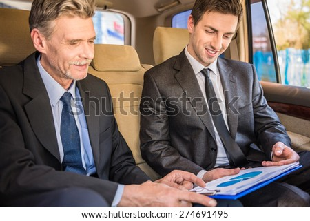 Two confident successful businessmen at a meeting sitting in the luxurious car and discussing churts. - stock photo