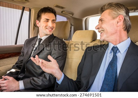 Two confident successful businessmen at a meeting sitting in the luxurious car and talking. - stock photo
