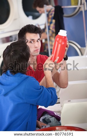 Two confused young men in laundromat read the instructions on detergent or conditioner canister - stock photo