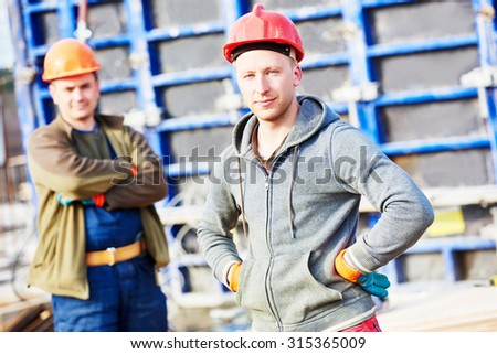 two construction builder labours workers at building site  - stock photo