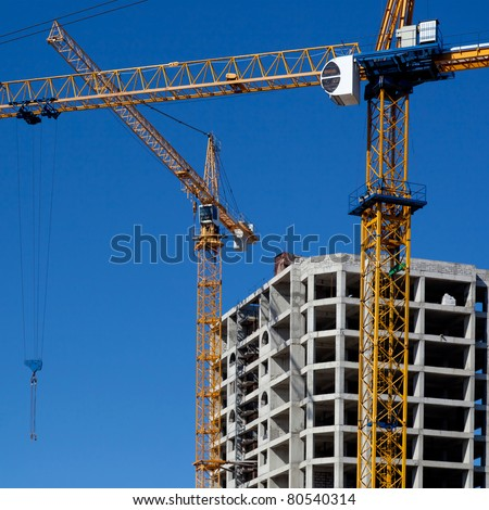 Two construction cranes rise above the building