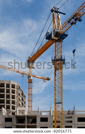 Two construction cranes rise above the building - stock photo