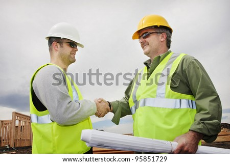 Two Construction Professionals Shaking Hands at the jobsite - stock photo