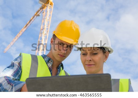 Two construction site workers in hard hats