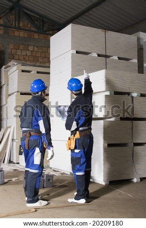 Two construction worker checking stock - stock photo