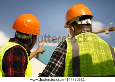Two construction worker wearing safety vest discussion, looking and pointing yellow crane at construction site - stock photo