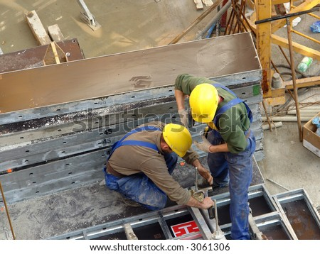Two construction workers assembling reinforcement elements - stock photo