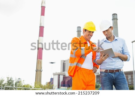 Two construction workers discussing over tablet PC at industry - stock photo