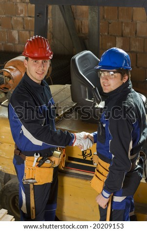 Two construction workers handshake. - stock photo