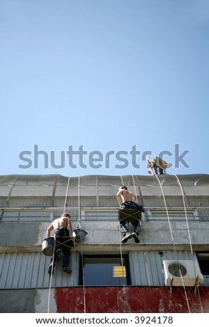 two construction workers on side of house - stock photo