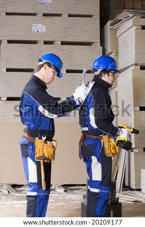 Two construction workers teamwork - stock photo