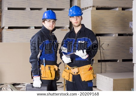 Two construction workers with check list - stock photo