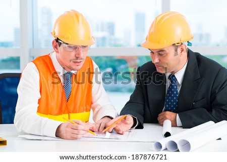 Two constructors drawing a blueprint of the building - stock photo