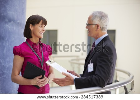 Two Consultants Meeting In Hospital Reception