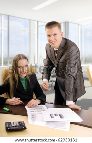 Two contemporary business people in an office discussing work