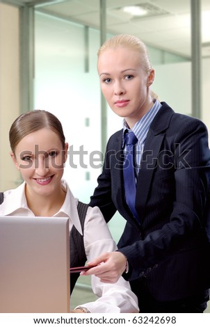 Two contemporary business women in an office discussing work on laptop looking on camera