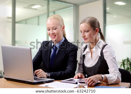 Two contemporary business women in an office discussing work sitting at the desk