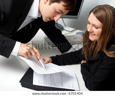 Two contemporary businesspeople discussing a document - stock photo