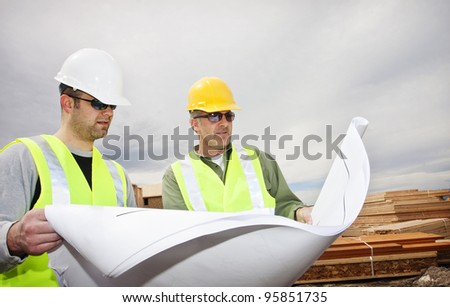 Two contractors reading construction plans at worksite - stock photo