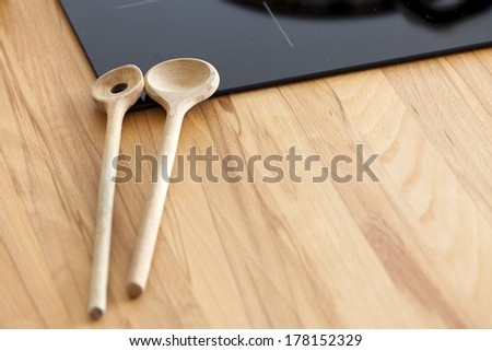 Two Cooking Spoon lies on Worktop nearby Ceramic Hob with Copy Space in the lower Area of the Image - stock photo