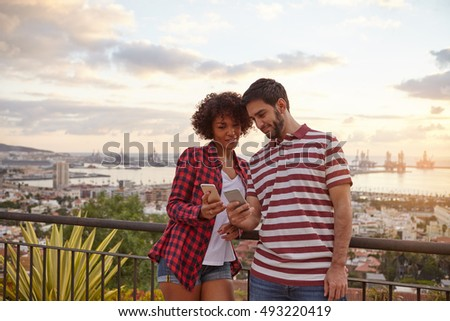 Two cool friends looking at each others cellphones while standing on a bridge that overlooks a city wearing casual clothing