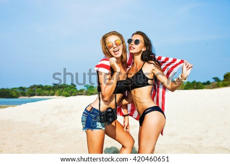 Two cool trendy hipster girls at the beach enjoying vacation on a tropical island, perfect tanned body, healthy skin, sexy stylish casual wear, bikini, blond and brunette with the camera, sunglasses - stock photo