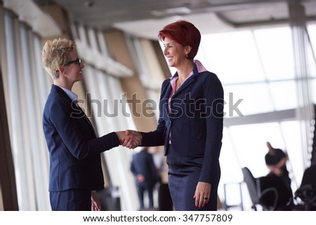 two corporate business woman at modern bright office interior make deal and handshake