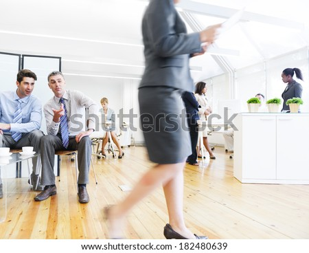 Two Corporate Men Staring and Gossiping About Their Female Colleague - stock photo