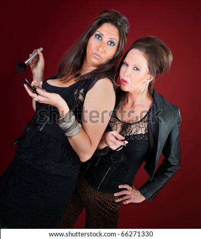Two cougars dressed in black do makeup and nails - stock photo
