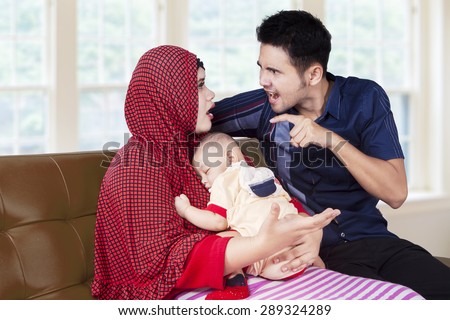 Two couple arguing at home while holding male baby and sitting on sofa - stock photo