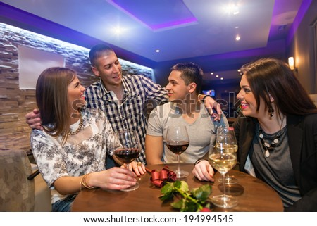 Two couple celebrating in cafe. Drinking wine and enjoying nightlife.