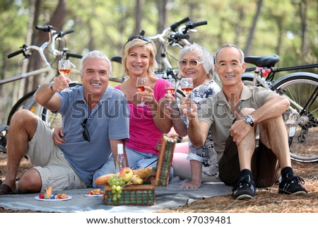 Two couple having picnic whilst on bike ride - stock photo