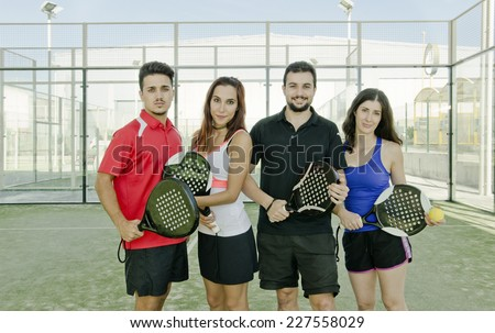 Two couple posing for paddle tennis match in court