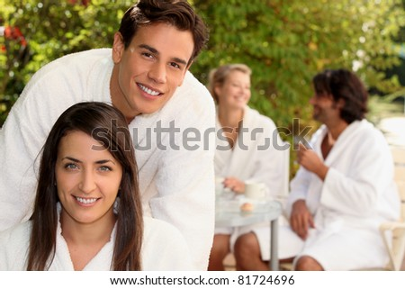 Two couple sat in garden wearing dressing gowns - stock photo