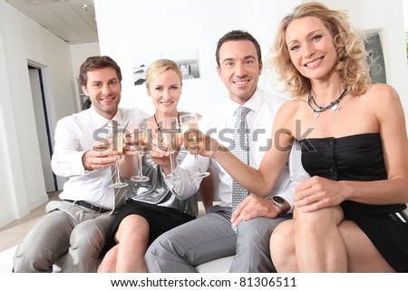 Two couple sitting holding up champagne glasses - stock photo