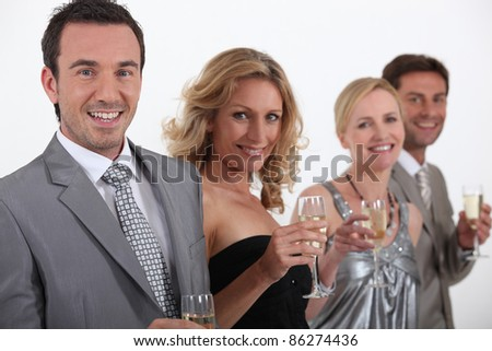 Two couple standing holding champagne classes - stock photo